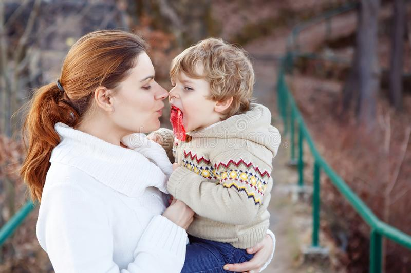 Mother and little son in park or forest, outdoors. Hugging and having fun together. Happy toddler boy and young mum, kid. And woman playing stock photography