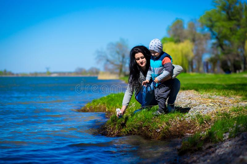 Mother and little son play outdoor near lake stock photo
