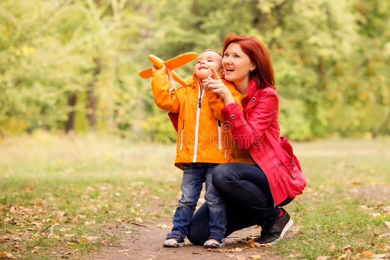 Mother and little son play together outdoors, mom explains how to launch toy airplane. Both are looking up and smiling stock photography