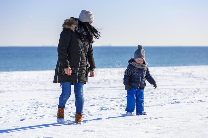 Mother with little son walking on snowy beach royalty free stock image