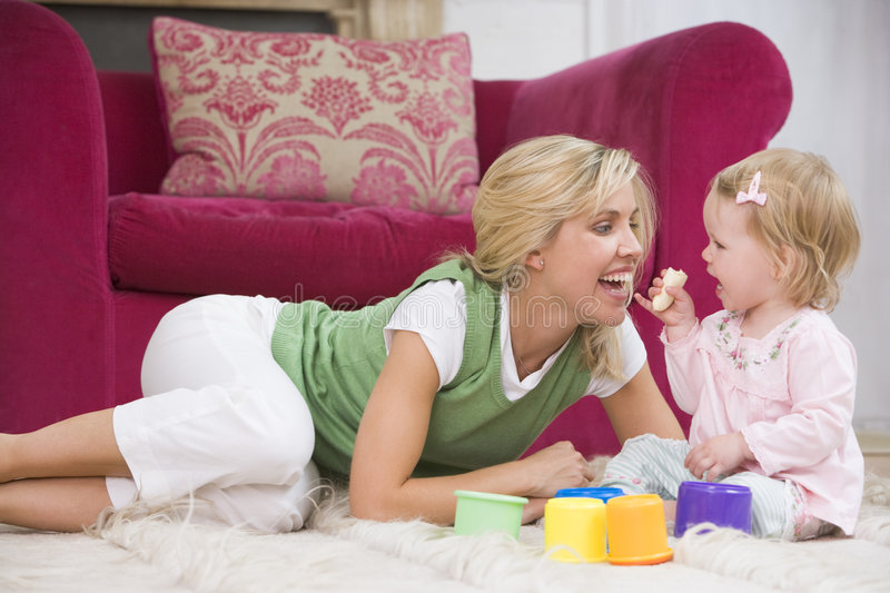 Mother in living room with baby eating banana royalty free stock images