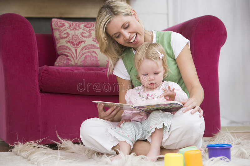 Mother in living room reading book with baby royalty free stock image