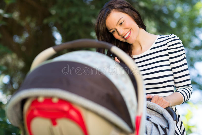 Mother Looking Into Baby Carriage In Park stock photography