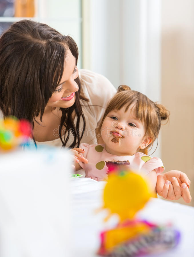 Mother Looking At Daughter Eating Cupcake royalty free stock image