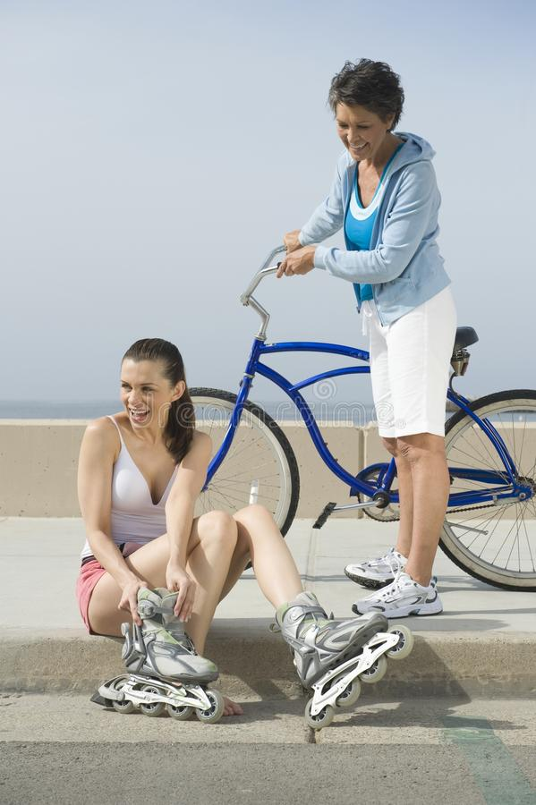 Mother Looking At Daughter Putting On Inline Skates stock images