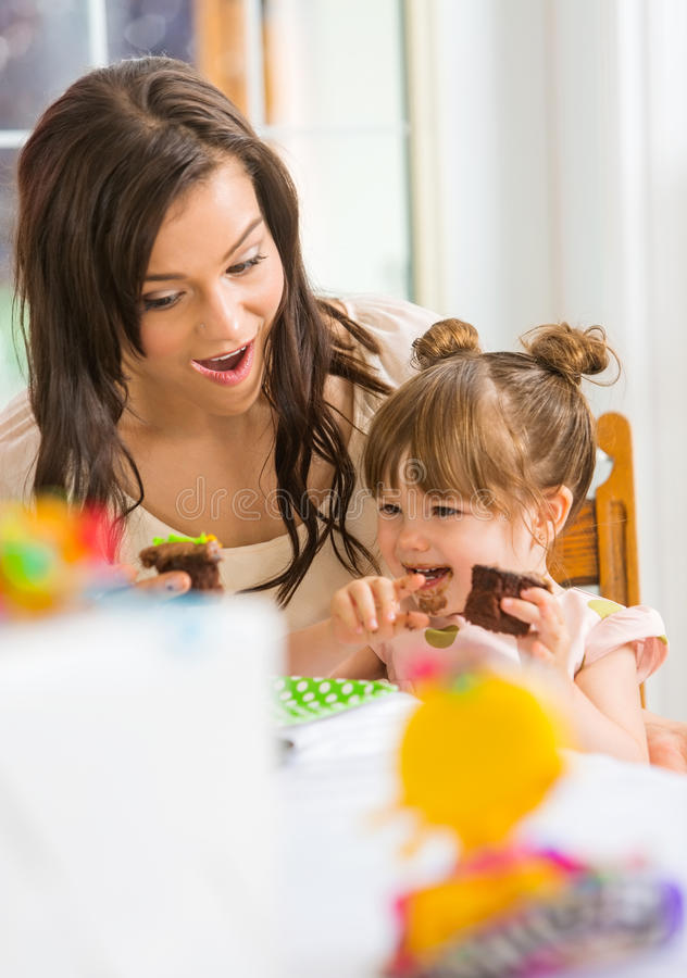 Mother Looking At Girl Eating Cupcake royalty free stock image