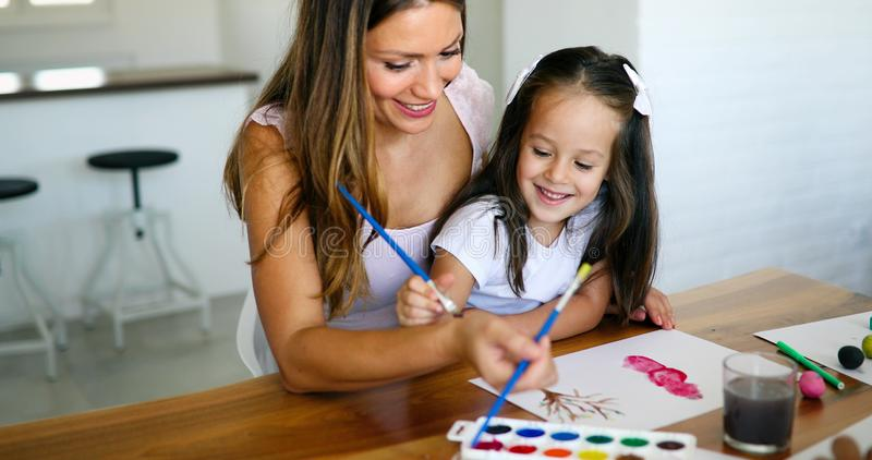 Mother looking how her child daughter drawing royalty free stock image