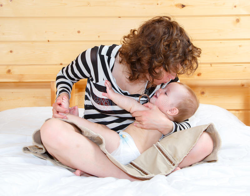 Mother in lotus position holds her cute baby. On the bed royalty free stock photography