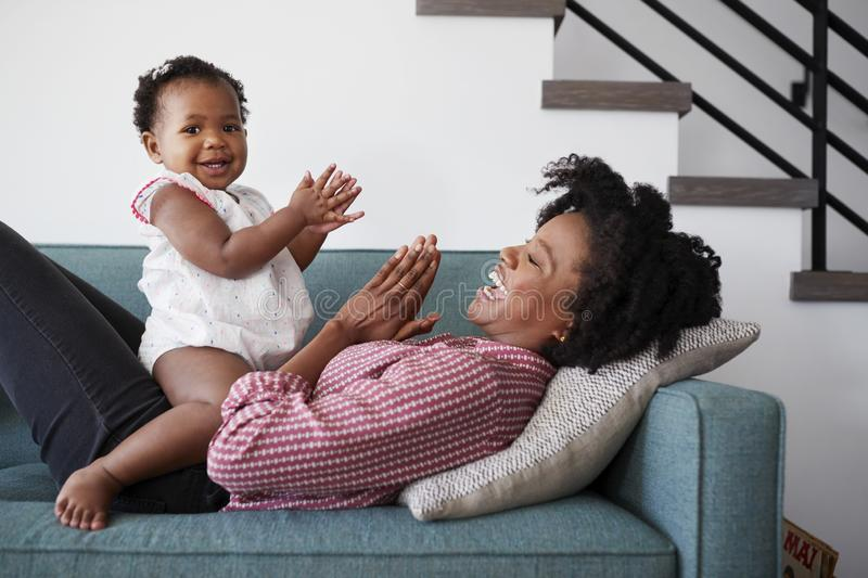 Mother Lying On Sofa At Home Playing Clapping Game With Baby Daughter royalty free stock photos