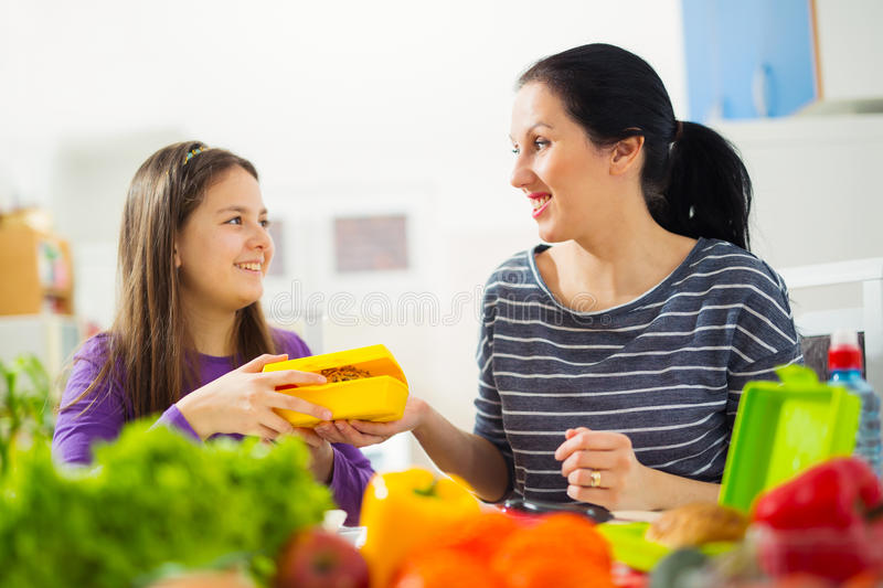 Mother making breakfast for her children in the morning and a sn. Ack for school at home stock photography