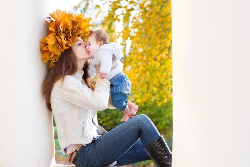Mother with maple leaves wreath kissing her baby royalty free stock photography