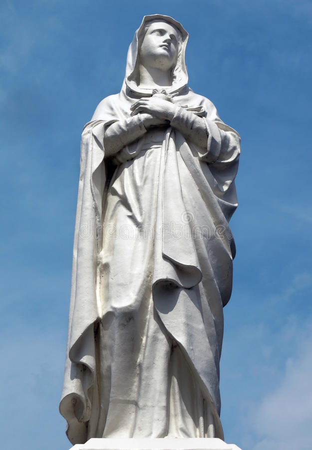 Mother Mary. White statue with blue sky background stock photography