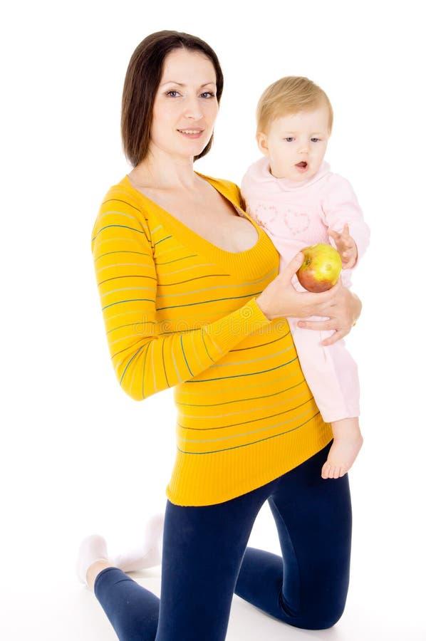 Mother matar äpplen för en behandla som ett barn royaltyfria foton