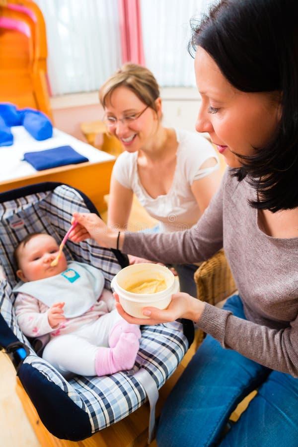 Mother matning behandla som ett barn arkivbild