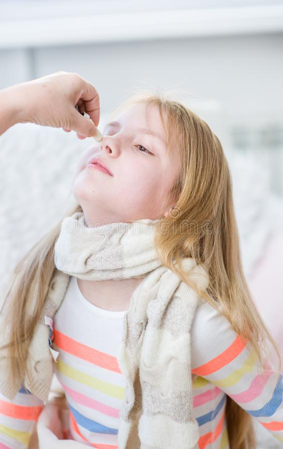 Mother medication drips into the nose girl.  stock photography