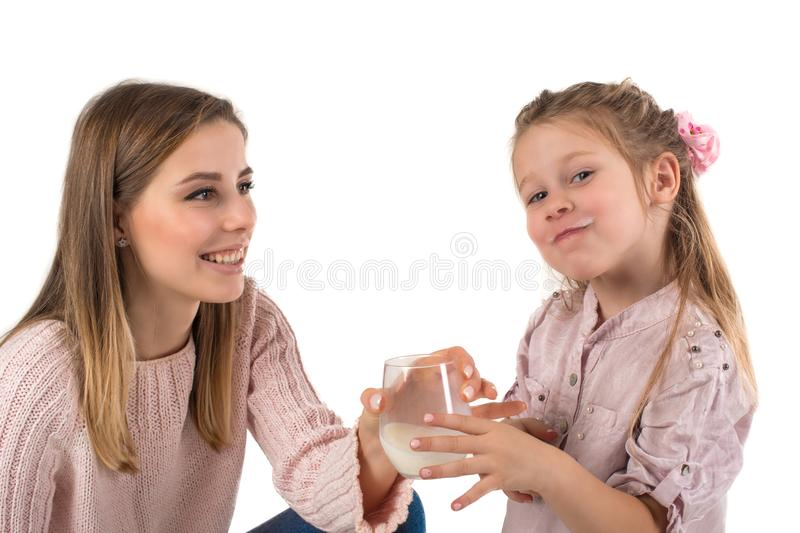 Mother milks to the daughter. The daughter with pleasure drinks milk royalty free stock image