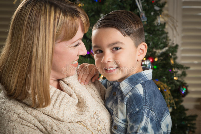 Mother and Mixed Race Son Hug Near Christmas Tree. Happy Mother and Mixed Race Son Hug Near Their Christmas Tree royalty free stock images