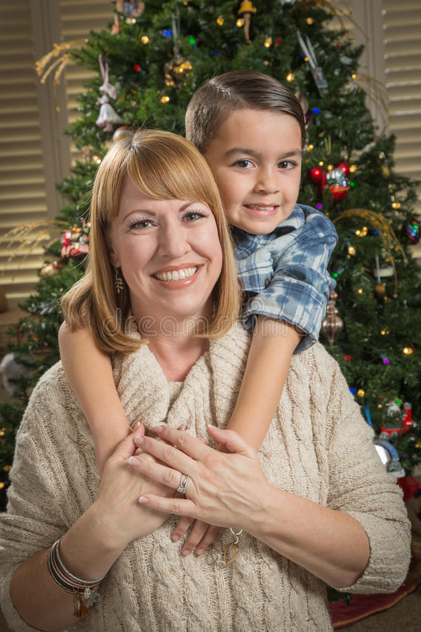 Mother and Mixed Race Son Hug Near Christmas Tree. Happy Mother and Mixed Race Son Hug Near Their Christmas Tree stock images