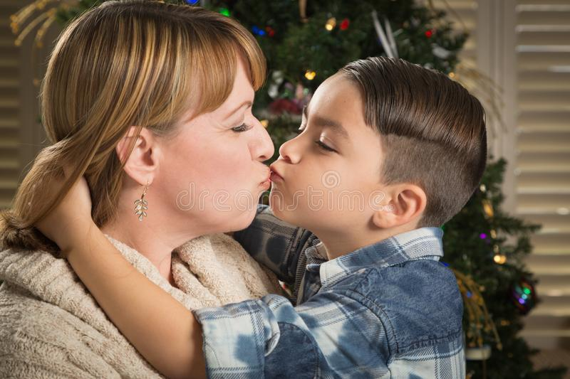 Mother and Mixed Race Son Hug Near Christmas Tree. Happy Mother and Mixed Race Son Hug Near Their Christmas Tree royalty free stock photo