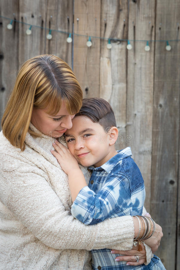 Mother and Mixed Race Son Hug Near Fence. Loving Mother and Mixed Race Son Hug Near Fence stock photo
