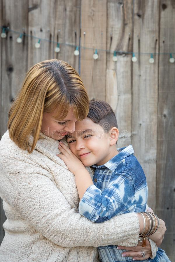 Mother and Mixed Race Son Hug Near Fence. Loving Mother and Mixed Race Son Hug Near Fence stock images