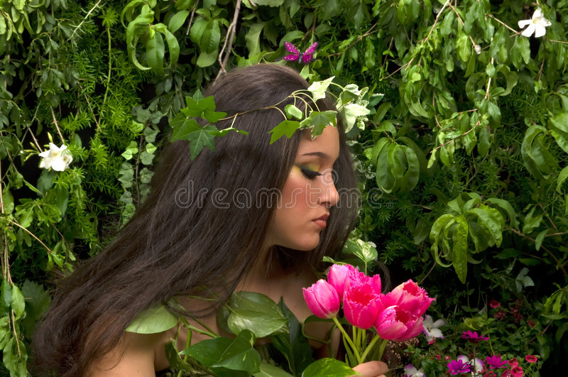 Mother Nature. Looking upon some of her many beautiful creations in her enchanted garden. This indoor studio shoot is a compilation of many fresh flowers, grass stock photography