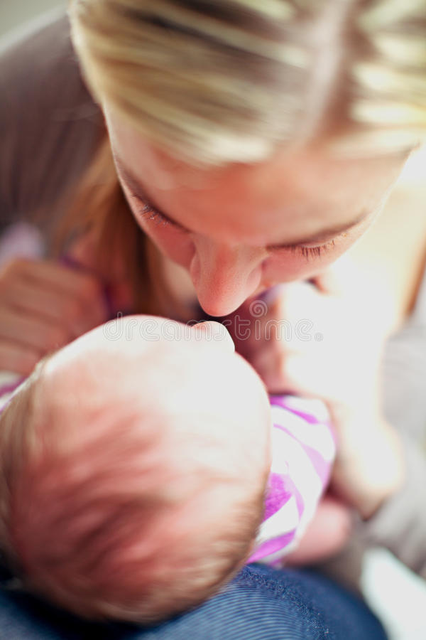 Mother and newborn baby bonding. Overhead view of a young mother and her tiny newborn baby bonding with their noses close together sharing an intimate tender stock photo
