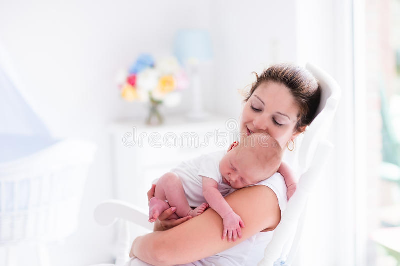 Mother and newborn baby in white nursery. Young mother holding her newborn child. Mom nursing baby. Woman and new born boy relax in a white bedroom with rocking royalty free stock photos