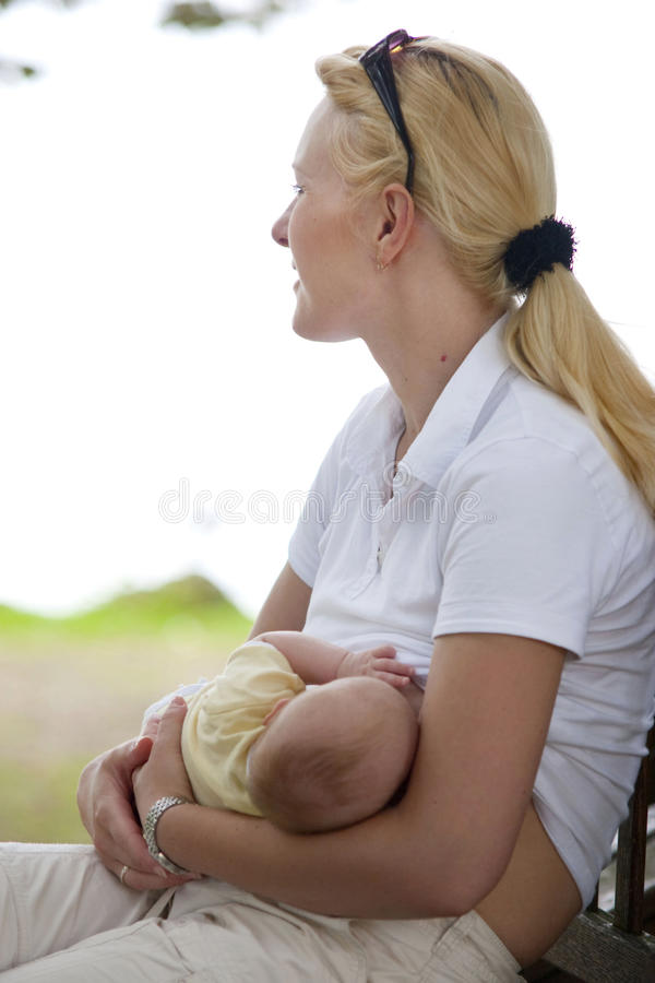 Mother nursing baby stock images