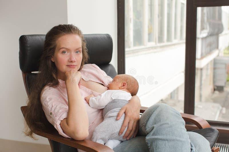 Mother nursing her newborn indoor royalty free stock image