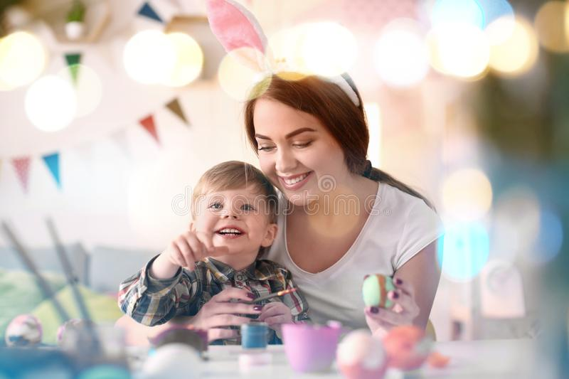 Mother painting Easter eggs with her child at table stock image