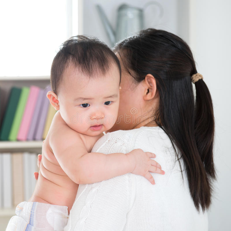 Mother pampering baby. Asian mother pampering six months old baby girl at home royalty free stock image