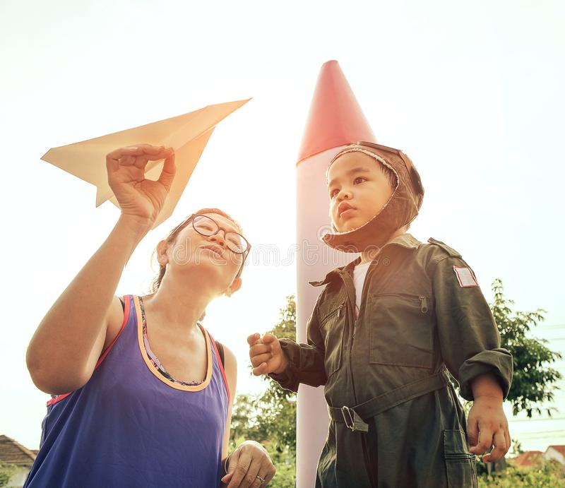 Mother with paper plane in hand playing with son wearing military pilot suit in garden stock photography