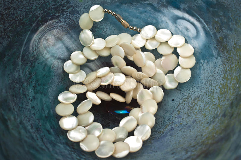 Mother-of-Pearl necklace. Mother-of Pearl Necklace in a colored glass bowl stock photos
