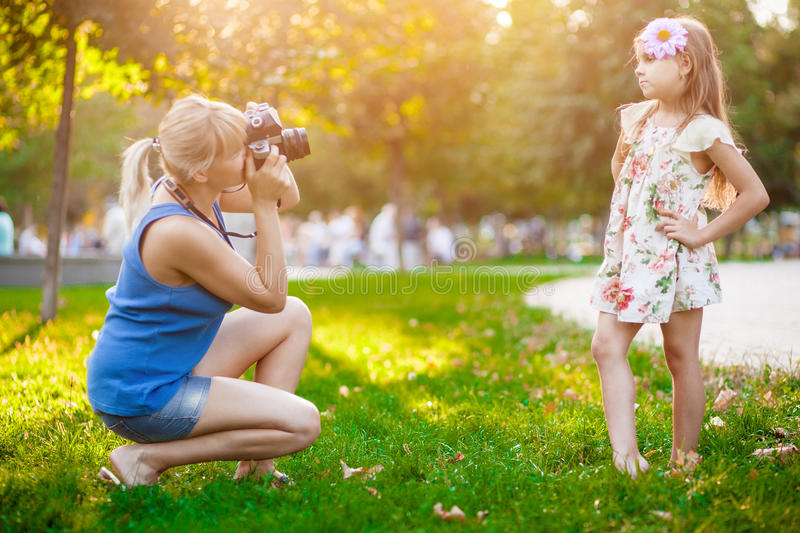 Mother photographing her daughter. In park royalty free stock image