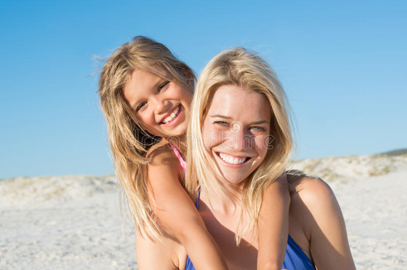 Mother piggybacking daughter royalty free stock images