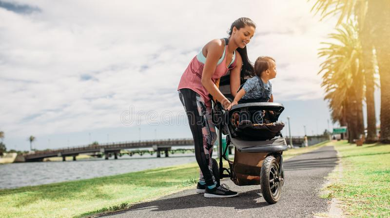 Mother placing her baby in a stroller. Woman taking her baby in a baby pram during her morning walk. Young mother with her baby in a stroller in park beside a stock photo