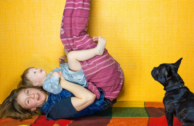 Mother play with daughter on the floor. lay on back. happy girl and woman have fun, laugh. family enjoy fitness stock photography