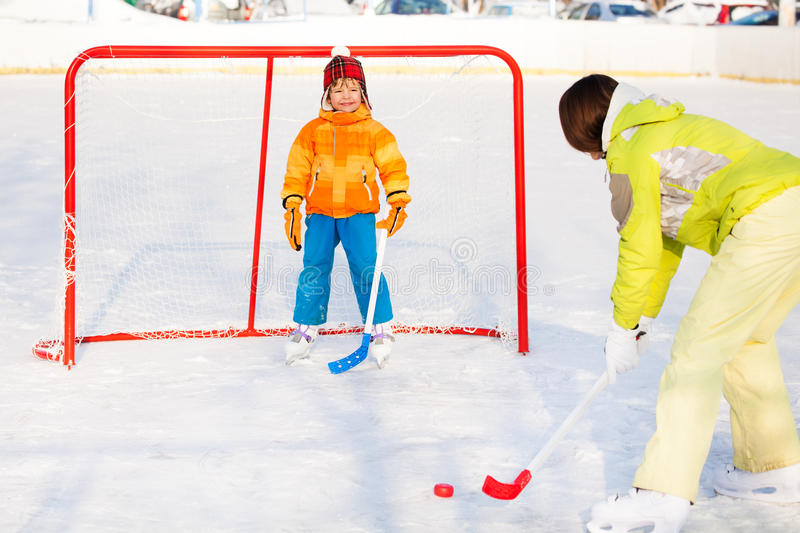 Mother play ice hockey with son outside. Mom teach little boy to play ice hockey and hold hockey stick standing near gates on ice royalty free stock photography