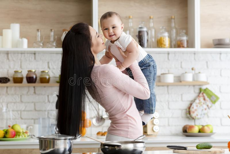Mother playing with adorable baby son in kitchen royalty free stock photography
