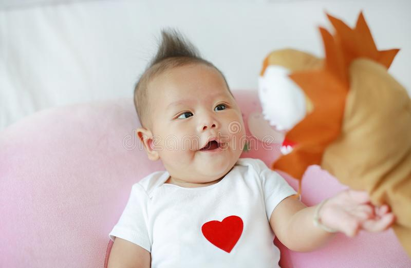 Mother playing animal puppet with her infant baby boy on the bed room at home.  stock photography