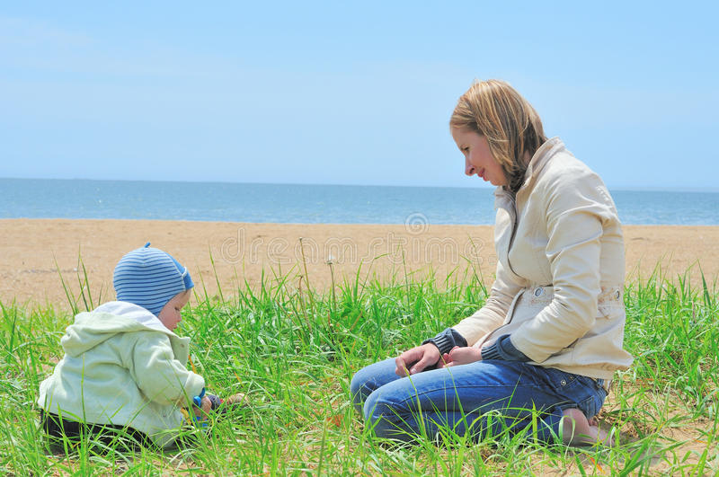 Mother playing with baby on the sand royalty free stock photography