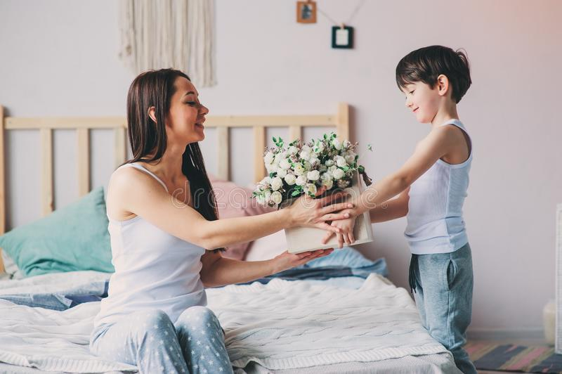 Mother playing with child son in bedroom. Happy family wearing pajamas stock image
