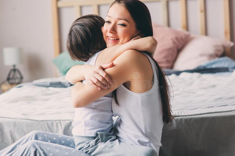 Mother playing with child son in bedroom. Happy family wearing pajamas royalty free stock image