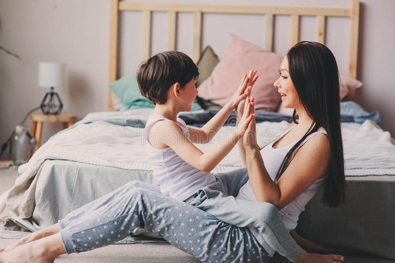 Mother playing with child son in bedroom. Happy family wearing pajamas stock photos