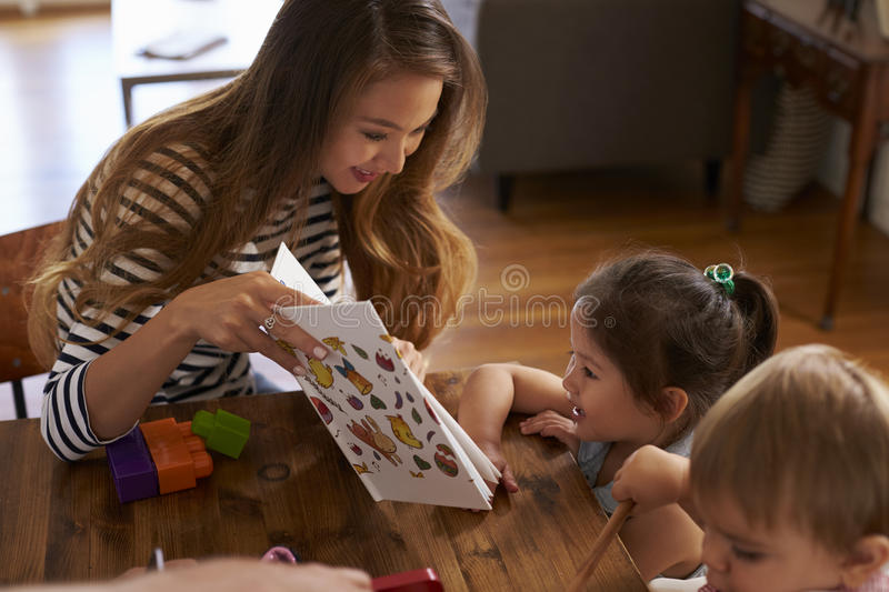 Mother Playing With Children On Table At Home royalty free stock image
