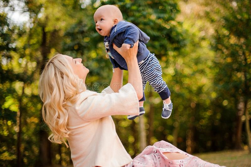 Mother playing with a cute baby son in a park royalty free stock image