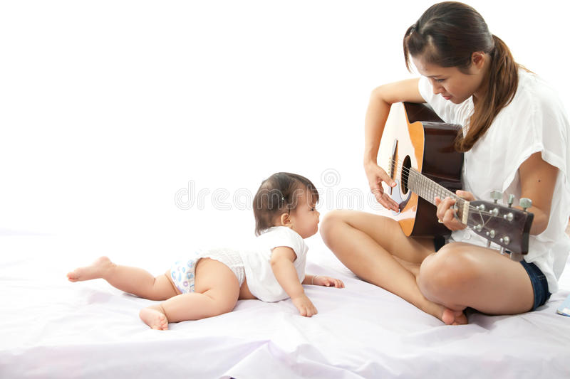 Mother is playing a guitar royalty free stock photography