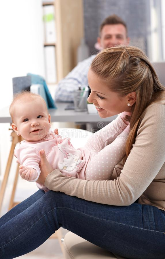 Mother playing with little daughter at home. Young mother holding baby daughter on lap, playing with her, having fun royalty free stock photo