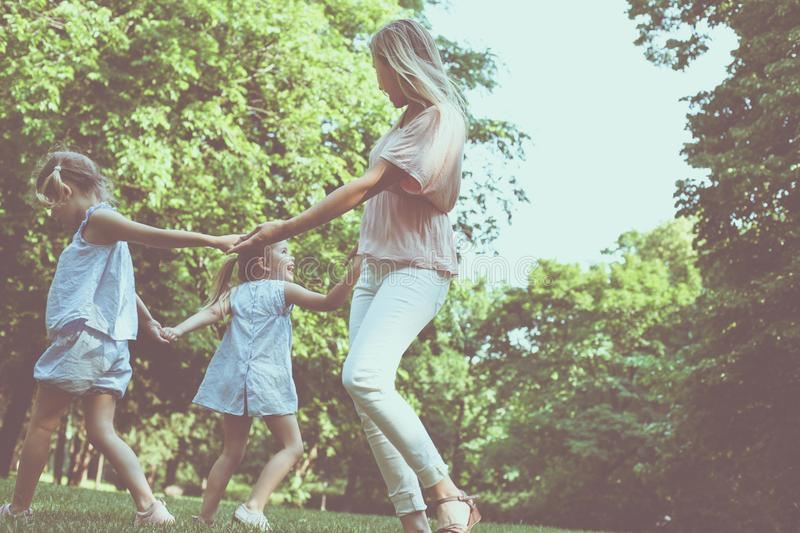 Mother playing on meadow with her two little daughter. stock images